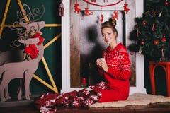 Den unga härliga kvinnan i röd varm pyjamas med scandinavianen smyckar att sitta nära den dekorativa spisen och att dricka varm k Royaltyfri Bild