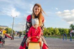 Den unga härliga modern i en tröja är spela, och rida på en gunga med hennes litet behandla som ett barn dottern i ett röd omslag Royaltyfri Bild
