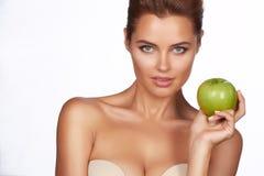Den unga härliga sexiga flickan med mörkt hår, kala skuldror och halsen som rymmer det stora gröna äpplet för att tycka om smaken Royaltyfria Bilder