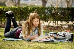 Den unga härliga studentflickan på universitetsområde parkerar gräs med böcker som studerar lycklig förberedande examen i utbildn Royaltyfri Bild