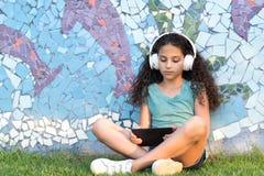 Den unga idérika tonåringflickan som sitter i staden, parkerar med bärbara datorn Tillfälligt bloggerbarn arkivfoton