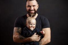 Den unga idrotts- fadern med förtjusande behandla som ett barn på svart bakgrund Royaltyfri Fotografi