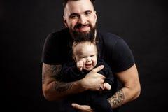 Den unga idrotts- fadern med förtjusande behandla som ett barn på svart bakgrund Royaltyfri Bild