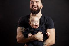 Den unga idrotts- fadern med förtjusande behandla som ett barn på svart bakgrund Arkivbild