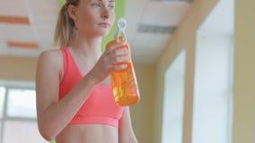Den unga idrotts- kvinnan är dricksvatten, når han har utbildat på den matta sporten lager videofilmer