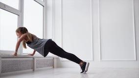 Den unga idrotts- kvinnan är driftig-upp på en fönsterfönsterbräda i ljust rum arkivfilmer