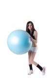 Den unga idrotts- kvinnan övade med en blå stabilitetsboll Arkivfoto