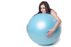 Den unga idrotts- kvinnan övade med en blå stabilitetsboll Arkivfoton