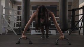 Den unga idrotts- kvinnan gör push-UPS med hantlar i idrottshallen lager videofilmer