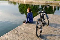 Den unga idrotts- kvinnan i sportswear sitter bredvid en cykel Royaltyfria Bilder