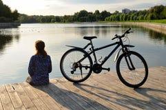 Den unga idrotts- kvinnan i sportswear sitter bredvid en cykel Royaltyfria Foton