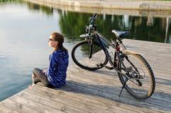 Den unga idrotts- kvinnan i sportswear sitter bredvid en cykel Royaltyfri Foto