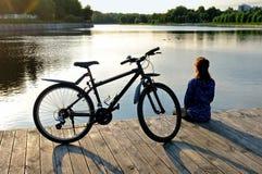 Den unga idrotts- kvinnan i sportswear sitter bredvid en cykel Royaltyfri Bild