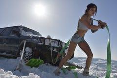 Den unga idrotts- kvinnan som drar bilen i vinter Arkivbild