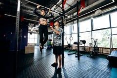 Den unga idrotts- mannen hjälper den spensliga nätta flickan att göra handtag upp på stången i idrottshallen royaltyfria foton