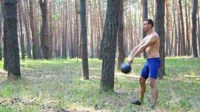 Den unga idrotts- mannen, med en kal naken torso, utför styrkaövningar med vikter, en beståndsdel av crossfit långsamt arkivfilmer
