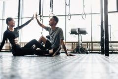 Den unga idrotts- mannen och den slanka flickan sitter på golvet och ger fem i idrottshallen royaltyfria foton
