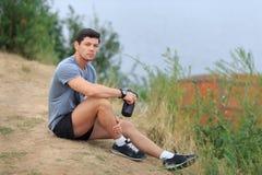Den unga idrottsman nen är trött och sitter begrepp för loppsportlivsstil Arkivfoton
