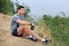 Den unga idrottsman nen är trött och sitter trassla ihop sportlivsstilbegreppet Fotografering för Bildbyråer