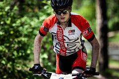 Den unga idrottsman nen rider en cykel Arkivfoto