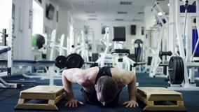Den unga idrottsman nen som gör extrahjälpen, skjuter ups i en idrottshall stock video