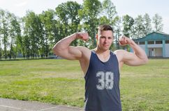 Den unga idrottsman nen visar biceps royaltyfri foto