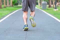 Den unga idrottsman nenmannen med springskor i parkerar den utomhus- manliga löparen som utanför joggar på vägen, asiatisk kondit royaltyfri bild
