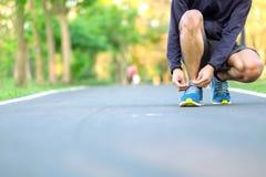 Den unga idrottsman nenmannen som binder springskor i, parkerar den utomhus- manliga löparen som är klar för att jogga på vägen u arkivbild