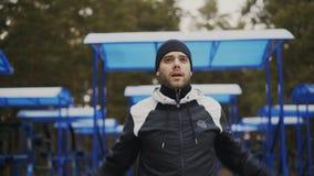 Den unga idrottsman nenmannen som värmer upp för genomkörareutbildning i vinter, parkerar arkivfilmer
