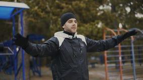Den unga idrottsman nenmannen som värmer upp för genomkörareutbildning i vinter, parkerar lager videofilmer