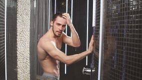 Den unga idrottsmannen tar en dusch, når han har joggat Handlaghår långsam rörelse arkivfilmer