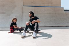 Den unga den ikl?dda fadern och hans sonen den tillf?lliga kl?derna placerar p? skateboarderna i en skridsko parkerar p? den soli arkivfoto