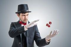 Den unga illusionisten eller trollkarlen visar magiskt trick med att få att sväva tärning royaltyfri foto