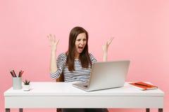 Den unga ilskna kvinnan, i att skrika för tillfällig kläder, har fördelande handarbete för problem på projekt med bärbar datorstu royaltyfri fotografi