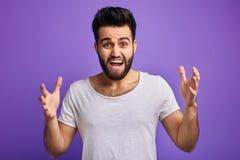 Den unga ilskna skäggiga mannen uttrycker hans negativa sinnesrörelser royaltyfri fotografi