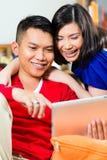 Asiatet kopplar ihop på soffan med en tabletPC Arkivbilder