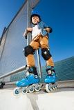 Den unga inline skateboradåkaren i hjälmen som poserar på skridskon, parkerar royaltyfria bilder
