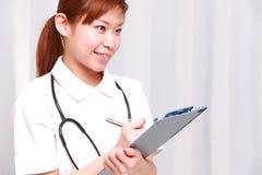 Den unga japanska sjuksköterskan fyller det medicinska diagrammet Arkivfoton