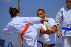 Den unga karateflickan bryter ett bräde Arkivbild