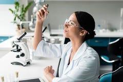 Den unga kemisten i skyddande exponeringsglas och vit täcker den undersökande provröret i labb arkivbilder