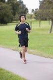 Den unga kinesiska mannen som joggar på, parkerar Arkivbilder