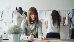 Den unga klädformgivaren är den upptagna teckningen skissar med blyertspennan, medan hennes kollega håller ögonen på bilder som i arkivfilmer