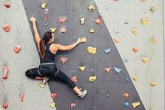 Den unga klättrarekvinnaklättringen på praktiskt vaggar i klättringmitten som bouldering arkivfoto