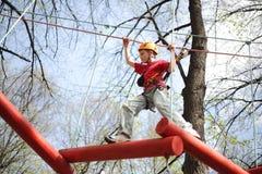 Den unga klättraren går skilfully på en upphängningbro Royaltyfri Bild