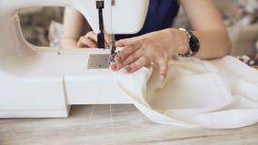 Den unga klädformgivaren och sömmerskakvinnan arbetar med symaskincloseupen i skräddarestudio stock video