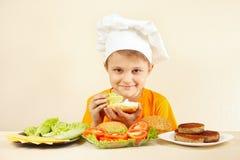 Den unga kocken sätter sallad på den stora smörgåsen Royaltyfri Foto