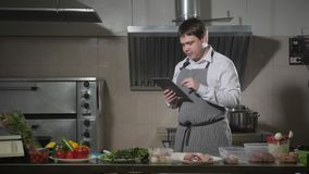 Den unga kocken ser på minnestavlan Matlagning i en restaurangkitche stock video