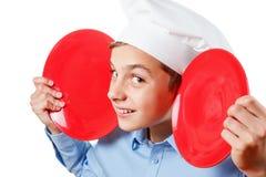 Den unga kocken som en grimassy apa, blidkar, kockens hatt Isolerad studio Royaltyfri Fotografi