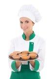 Den unga kockkvinnan i enhetligt hållande magasin med muffin isolerade nolla Arkivbilder