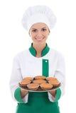 Den unga kockkvinnan i enhetligt visningmagasin med muffin isolerade nolla Royaltyfri Foto